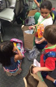 Summer Enrichment Mission children open backpacks - Kirk of Kildaire Presbyterian, a church in Cary NC